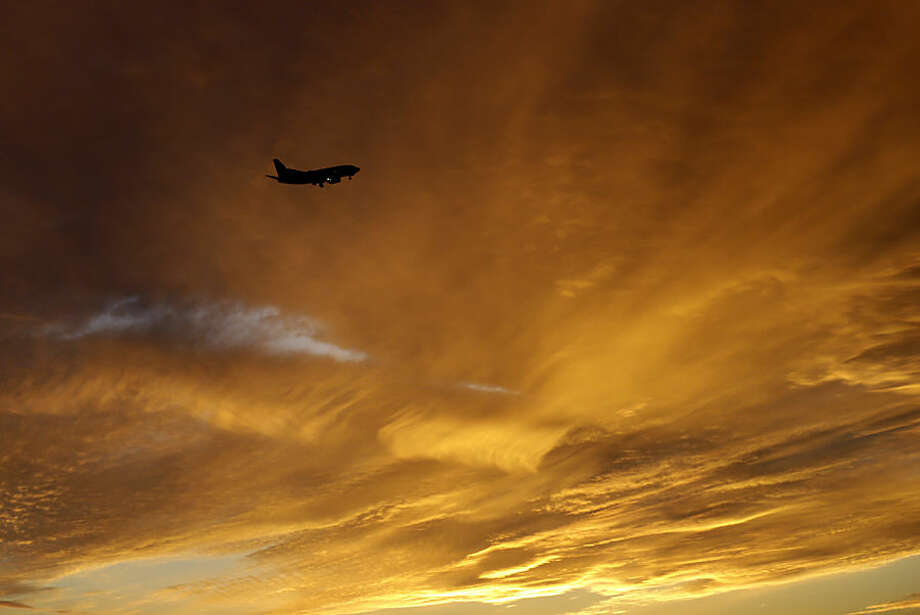 An airliner approaches Kansas City International Airport during sunset in Kansas City, Mo., Wednesday, Nov. 12, 2014. (AP Photo/Orlin Wagner)