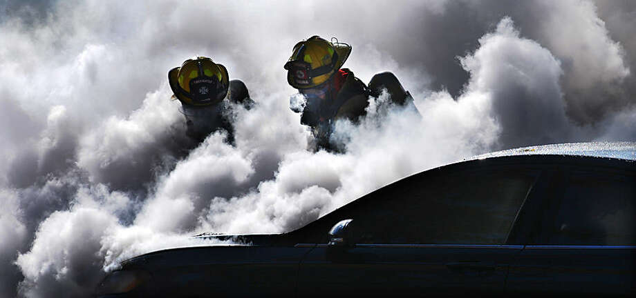 Firefighters are partially obscured by smoke Tuesday, Nov. 11, 2014, as they work to extinguish a burning car in Salina, Kan. (AP Photo/Salina Journal, Tom Dorsey)