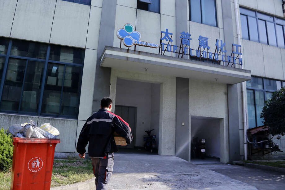 This photo taken Oct. 13, 2014 shoes a delivery man walking in front of Shanghai Top Fluoro company in Shanghai, China. Shanghai Top Fluoro is described by Tianhe as a trading company that buys as much as $100 million in high-priced chemicals from Tianhe every year. (AP Photo)