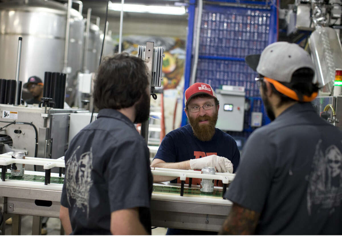 In this Wednesday, Nov. 12, 2014 photo, DC Brau Brewing Co. employees, from left, Jake Agger, Jason Budman, and Chad Hooper, talk in the the canning area at the brewery in Washington, D.C. The district's small business health insurance exchange helped DC Brau offer more than 50 insurance options to its employees starting in September. That's a massive leap from the two choices it usually cobbled together. (AP Photo/Carolyn Kaster)
