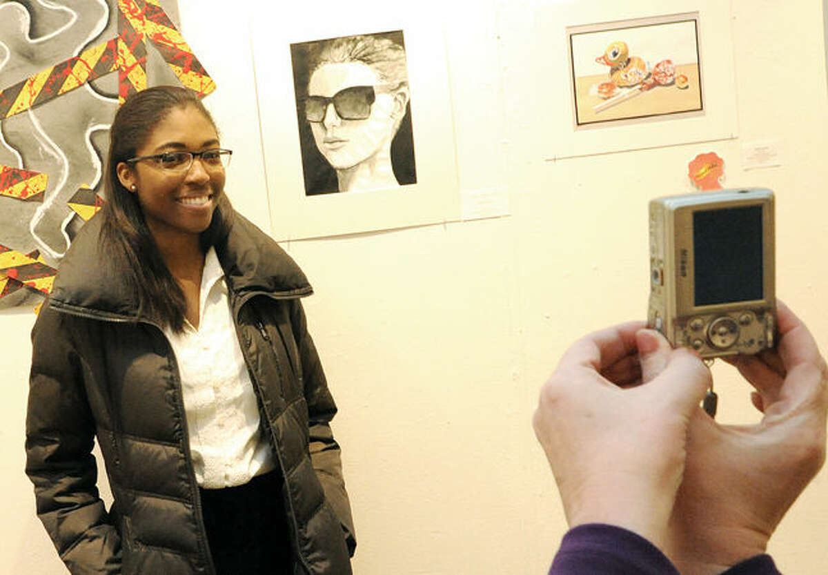 """Stamford High School 12th-grader Sabina Pierre-Louis poses for a photo in front of her acrylic painting titled """"Sunglasses"""" at the Silvermine School of Art Sunday."""