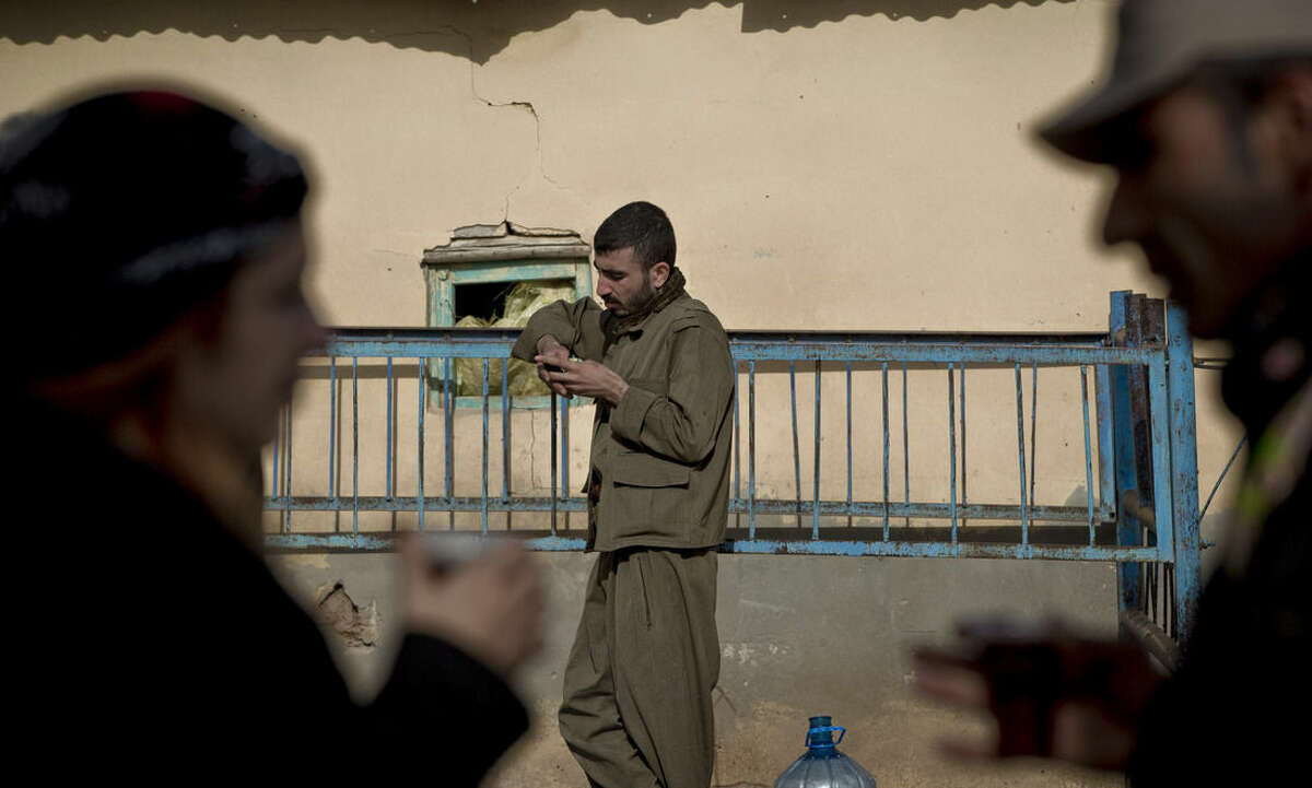 In this picture taken on Nov. 3, 2014 a Kurdish man handles a mobile device in Caykara, on the Turkey-Syria border. Hundreds of volunteers, predominantly Kurdish Turks, who have traveled from all over southeastern Turkey and even from Istanbul, keep watch on the border with Syria, looking out for potential fighters of the extremist Islamic State group attempting to cross into Kobani, besieged since mid-September by IS and defended by Kurdish Syrian fighters known as the People's Protection Units. (AP Photo/Vadim Ghirda)