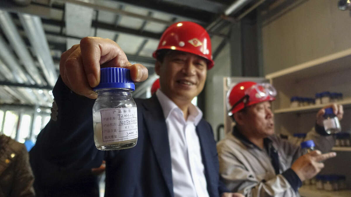 In this photo taken Oct. 24, 2014, Tianhe Chief Executive Wei Xuan shows journalists a sample of one of the specialty chemicals the company manufactures at its 800,000 square meter Jinzhou plant in China. The pitch to investors described the company on the verge of spectacular success. Tianhe Chemicals Group Ltd. boasted rock-bottom labor costs, unique manufacturing techniques and net profit margins triple those of competitors. (AP Photo/Erika Kinetz)