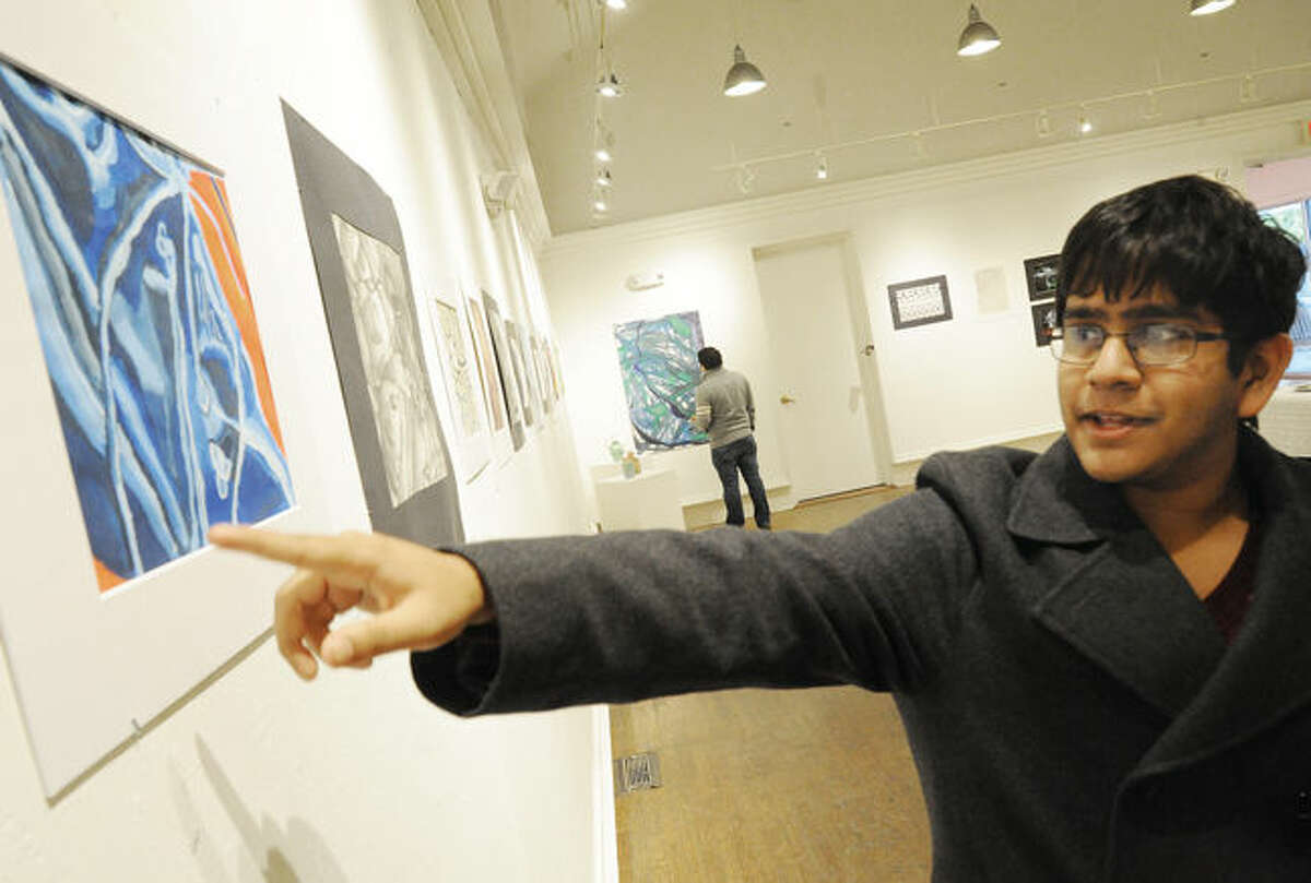 """Westhill High School 10th-grader Siddarth Suresh points out his mixed media project """"Abstracted Boot"""" at the Silvermine School of Art"""