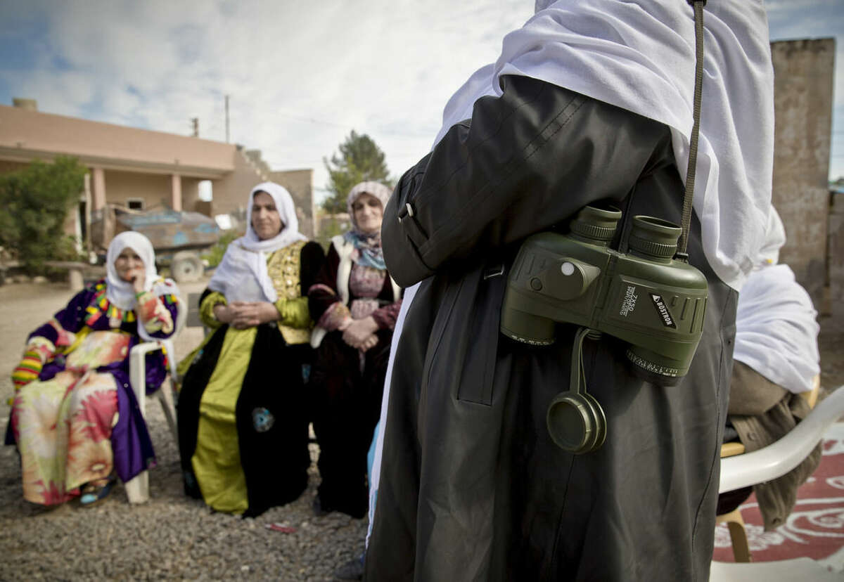 In this picture taken on Nov. 3, 2014, a member of the Peace Mothers, a Kurdish civil rights group that promotes peace between Turkey's ethnic groups, carries binoculars in the village of Caykara, on the Turkey-Syria border. Hundreds of volunteers, predominantly Kurdish Turks, who have traveled from all over southeastern Turkey and even from Istanbul, keep watch on the border with Syria, looking out for potential fighters of the extremist Islamic State group attempting to cross into Kobani, besieged since mid-September by IS and defended by Kurdish Syrian fighters known as the People's Protection Units. (AP Photo/Vadim Ghirda)