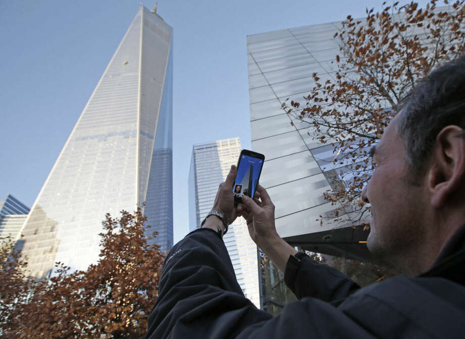 Tomas Vruns, from Muenster, Germany, uses his cell phone to take a picture of 1 World Trade Center where a scaffolding still dangled hours after two window washers were rescued by firefighters who sawed through a window to reach them, Wednesday, Nov. 12, 2014, in New York. The accident, which officials said was caused by a malfunctioning cable, happened little more than a week after workers began moving into the nation's tallest building. (AP Photo/Kathy Willens)
