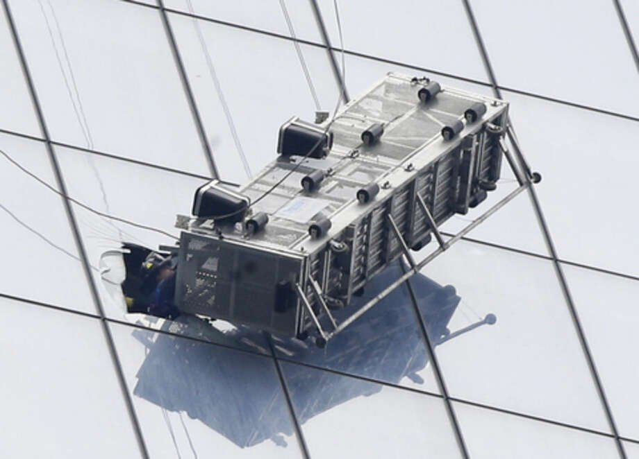 A firefighter reaches through a cut-out window into a dangling work basket to rescue two workers from the 60th floor of 1 World Trade in New York, Wednesday, Nov. 12, 2014. The two window washers were trapped for more than an hour. The dramatic rescue occurred on the south side of the 1,776-foot, 104-story building, where the open-topped platform hung at about a 45-degree angle and swayed slightly in the wind. (AP Photo/Kathy Willens)