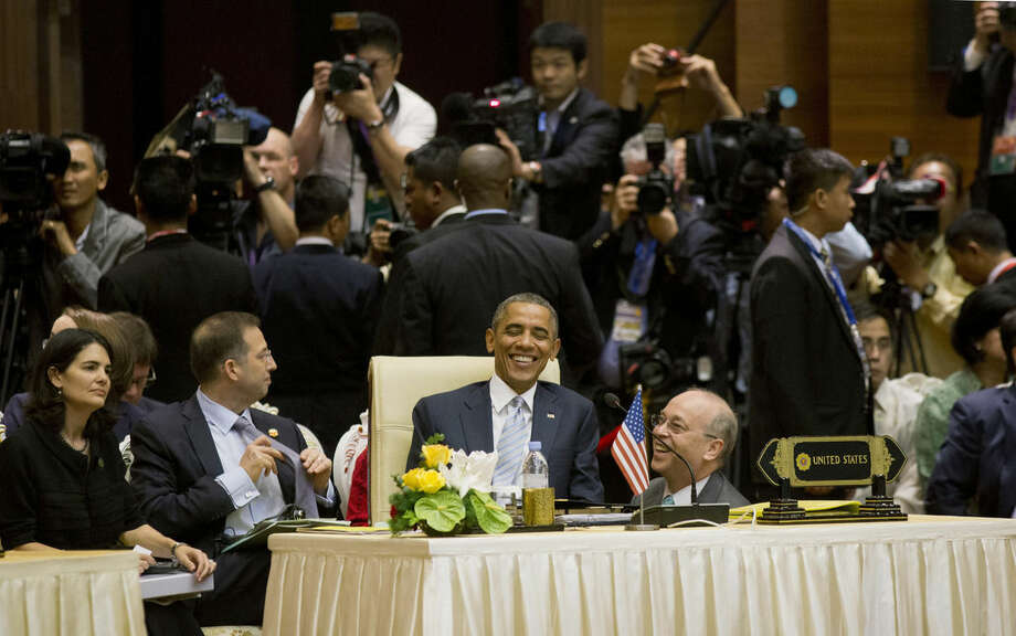 U.S. President Barack Obama, center, smiles as he speaks with Daniel R. Russel, U.S. Assistant Secretary of State for the Bureau of East Asian and Pacific Affairs, right, as he attends an East Asia Summit Plenary at the Myanmar International Convention Center, Thursday, Nov. 13, 2014 in Naypyitaw, Myanmar. (AP Photo/Pablo Martinez Monsivais)
