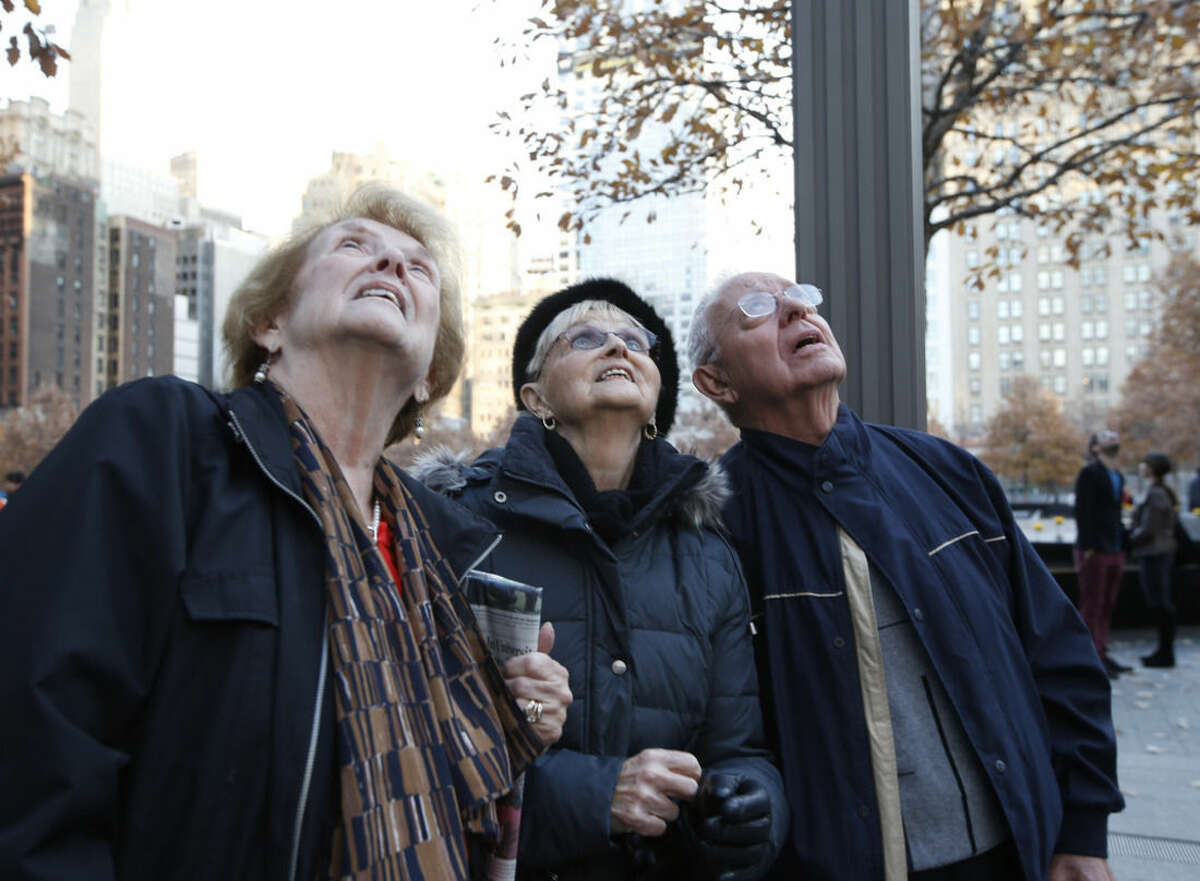 Peggy Stewart, left, joins friends Eve and Cos Contento as they gaze up at 1 World Trade Center where a scaffolding still dangled hours after two window washers were rescued by firefighters who sawed through a window to reach them, Wednesday, Nov. 12, 2014, in New York. (AP Photo/Kathy Willens)