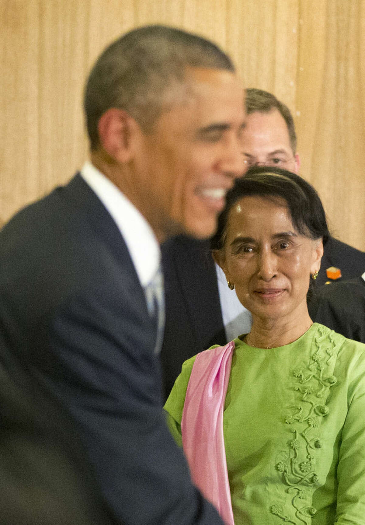 Myanmar's opposition leader Aung San Suu Kyi, right, looks at U.S. President Barack Obama greet participants following a meeting at Parliamentary Resource Center, Thursday, Nov. 13, 2014 in Naypyitaw, Myanmar. (AP Photo/Pablo Martinez Monsivais)