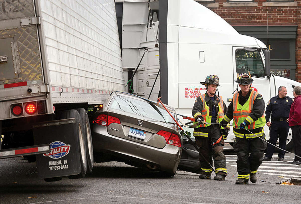 Hour photo / Erik Trautmann A Honda Civic gets caught underneath tractor trailer at Route 1 and Riverside Ave closing the intersection in Westport Thursday afternoon. The driver of the Civic escaped without injury.