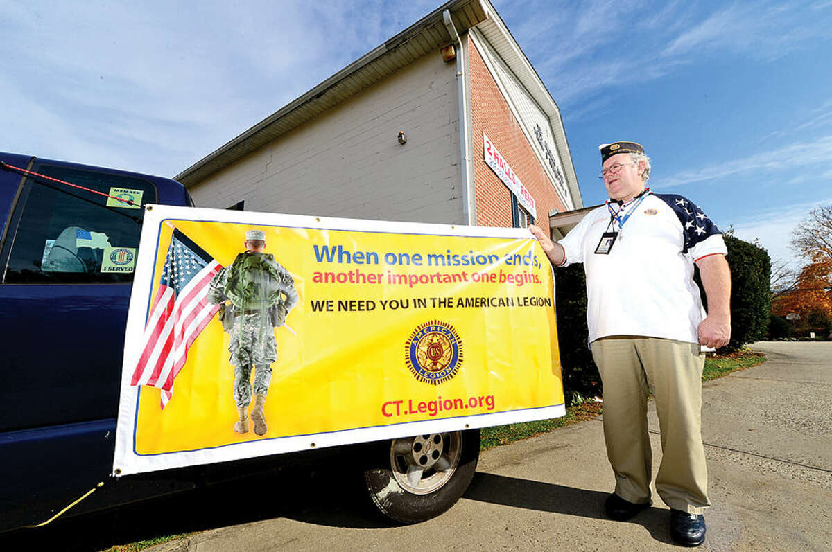 Hour photo / Erik Trautmann Post Commander Richard Olson straightens a banner outside the Frank C. Godfrey American Legion Post 12 as they host a 3rd District Post Membership Revitalization Program Thursday. Post members from across the state were on hand to contact prospective and new veterans to join or transfer into the local Posts. The event continues through the Saturday, November 15th from 10:00 AM to 4:30 PM each day.