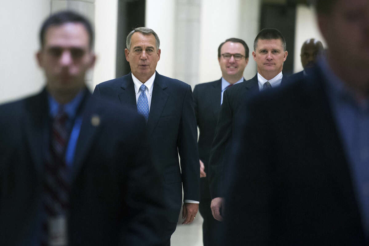 FILE - In this Nov. 6, 2014 file photo, House Speaker John Boehner of Ohio walks with advisers and security to a news conference on Capitol Hill in Washington. In the short-on-specifics elections just ended, the economy was the main issue, Republicans ran against President Barack Obama and Democrats campaigned against the billionaire Koch brothers. That leaves the new GOP majority in Congress with a mandate to improve the economy, yet without a national consensus on how to go about it. At the same time, shrunken Democratic minorities in the House and Senate are in search of a more appealing approach. (AP Photo/Cliff Owen, File)
