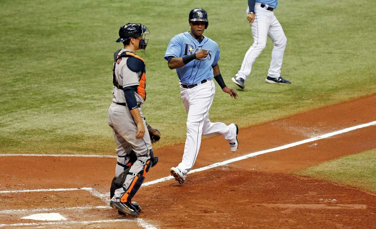 ST. PETERSBURG, FL - JUNE 12: Tim Beckham #1 of the Tampa Bay Rays scores as Jason Castro #15 of the Houston Astros looks on during the fifth inning of a game at Tropicana Field on June 12, 2016 in St. Petersburg, Florida.