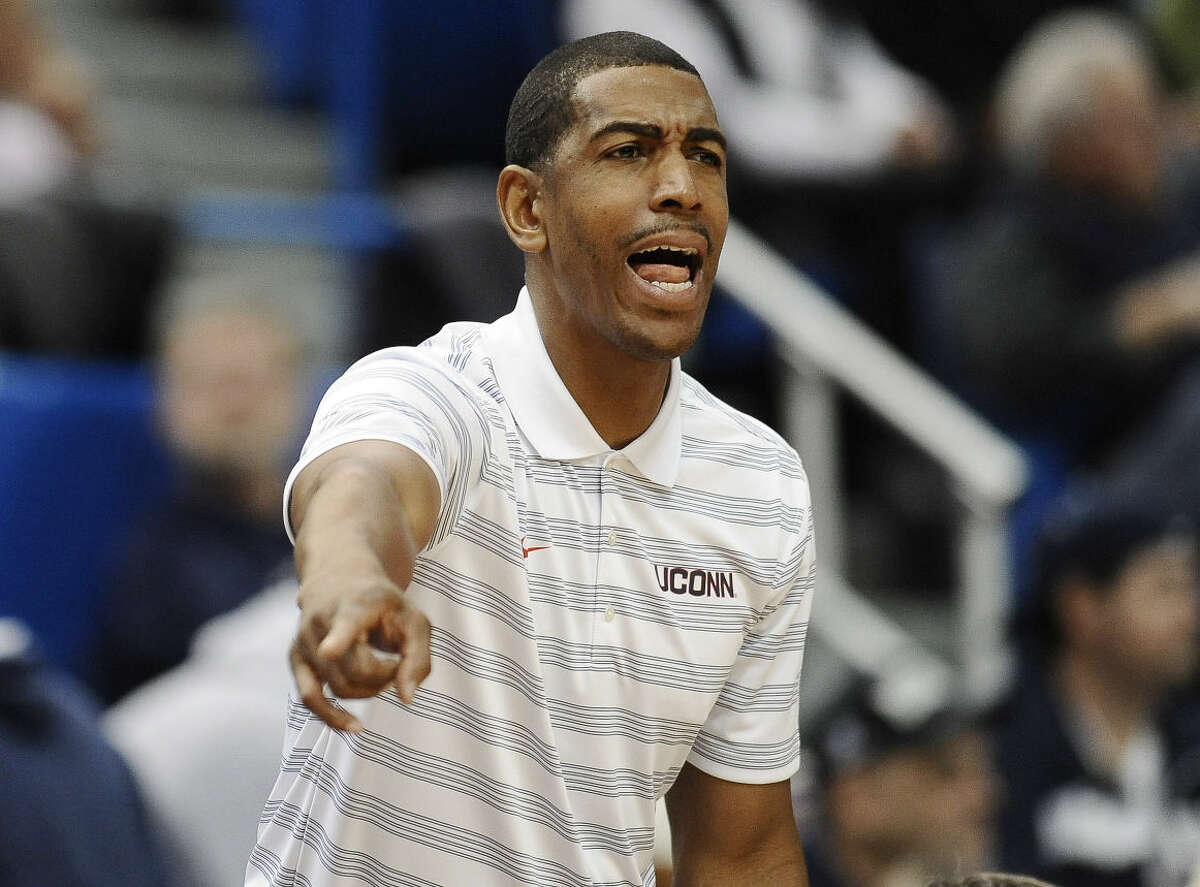 Connecticut head coach Kevin Ollie calls out to his team during the second half of an NCAA college basketball game, Sunday, Nov. 9, 2014, in Hartford, Conn. Connecticut won 68-59. (AP Photo/Jessica Hill)