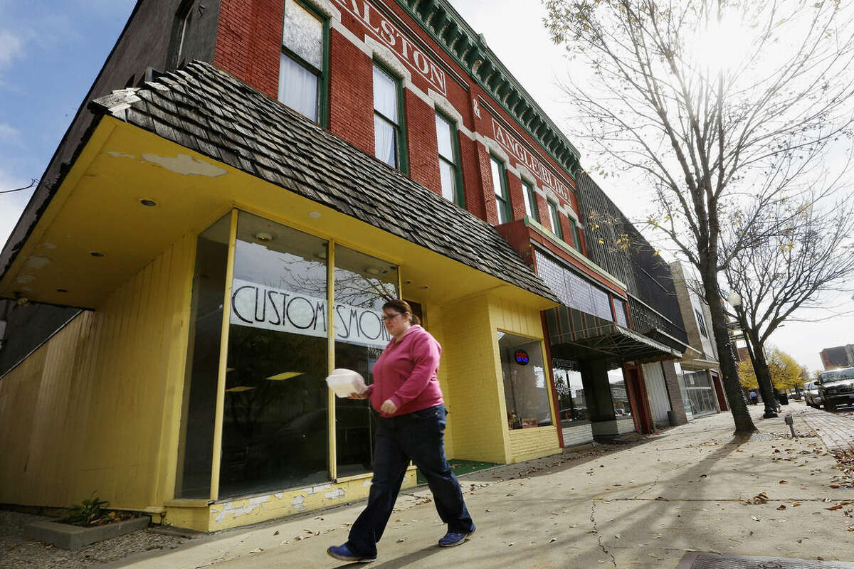 In this Oct. 23, 2014 photo, a woman walks past businesses in downtown in Danville, Ill., where there still are many vacant buildings. Many young people have moved away as manufacturers that provided thousands of well-paying, middle class jobs have closed, but the city is working to attract new businesses and give residents a reason to stay. (AP Photo/Seth Perlman)