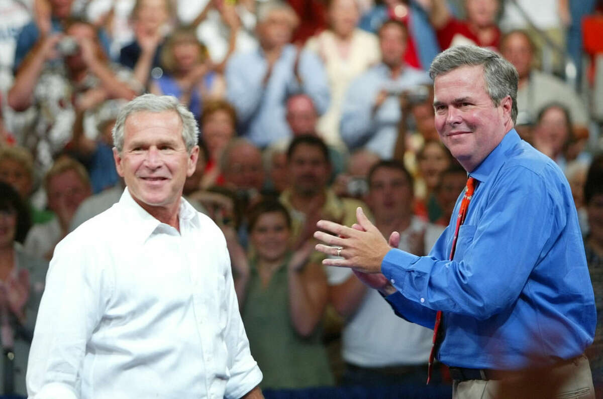 FILE - In this Aug. 10, 2004 file photo, President George W. Bush, left, is introduced by his brother Florida Gov. Jeb Bush, right, at 'Ask President Bush' campaign rally, at Okaloosa-Walton Community College Gymnasium in Niceville, Fla. President George W. Bush is giving even odds to an attempt at a family legacy as part of the 2016 White House campaign, saying Sunday Nov. 9, 2014 on