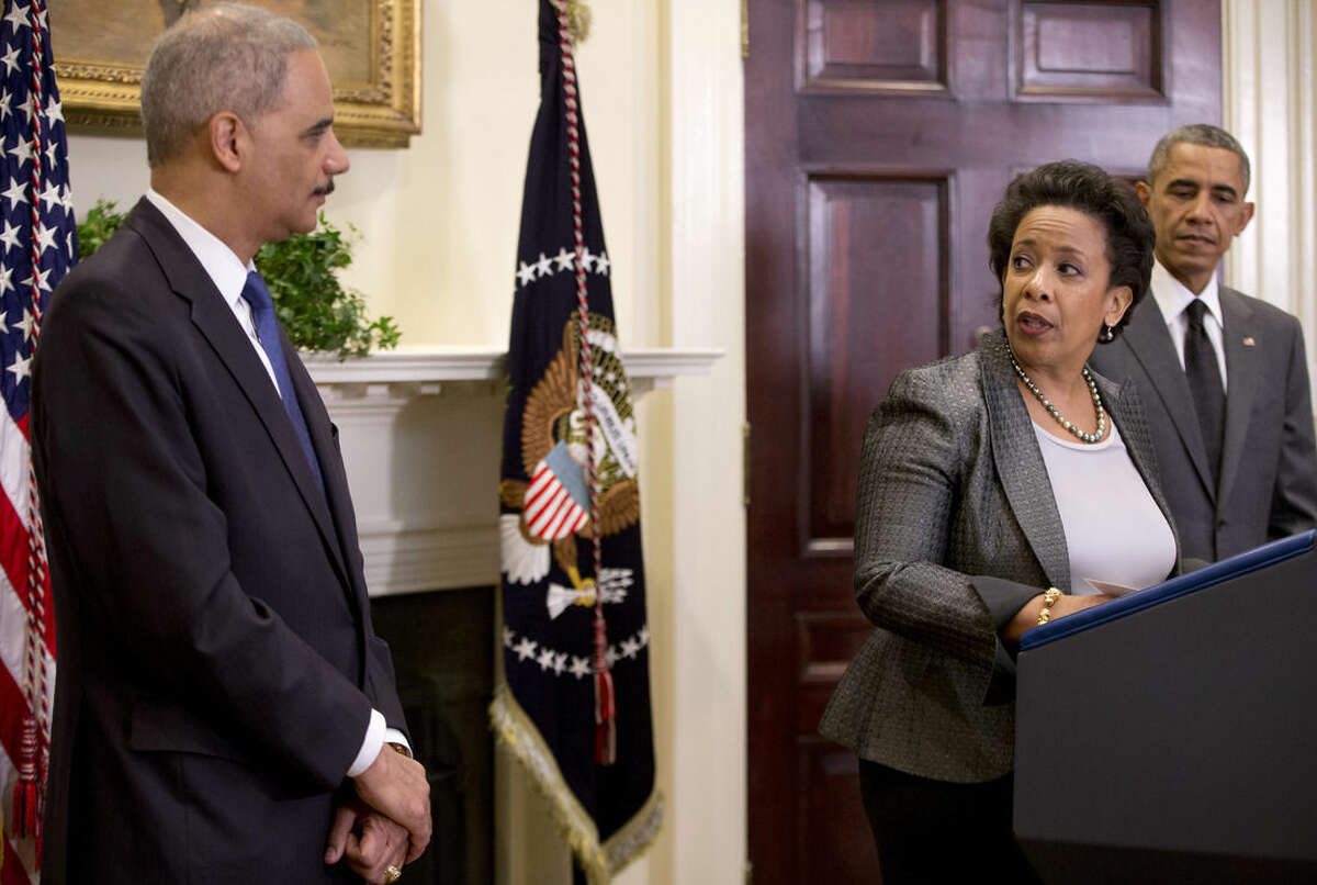 US Attorney Loretta Lynch, center, looks to Attorney General Eric Holder as with President Barack Obama at right, in the Roosevelt Room of the White House in Washington, Saturday, Nov. 8, 2014, where the president announced that he will nominate Lynch to replace Holder as Attorney General. (AP Photo/Carolyn Kaster)