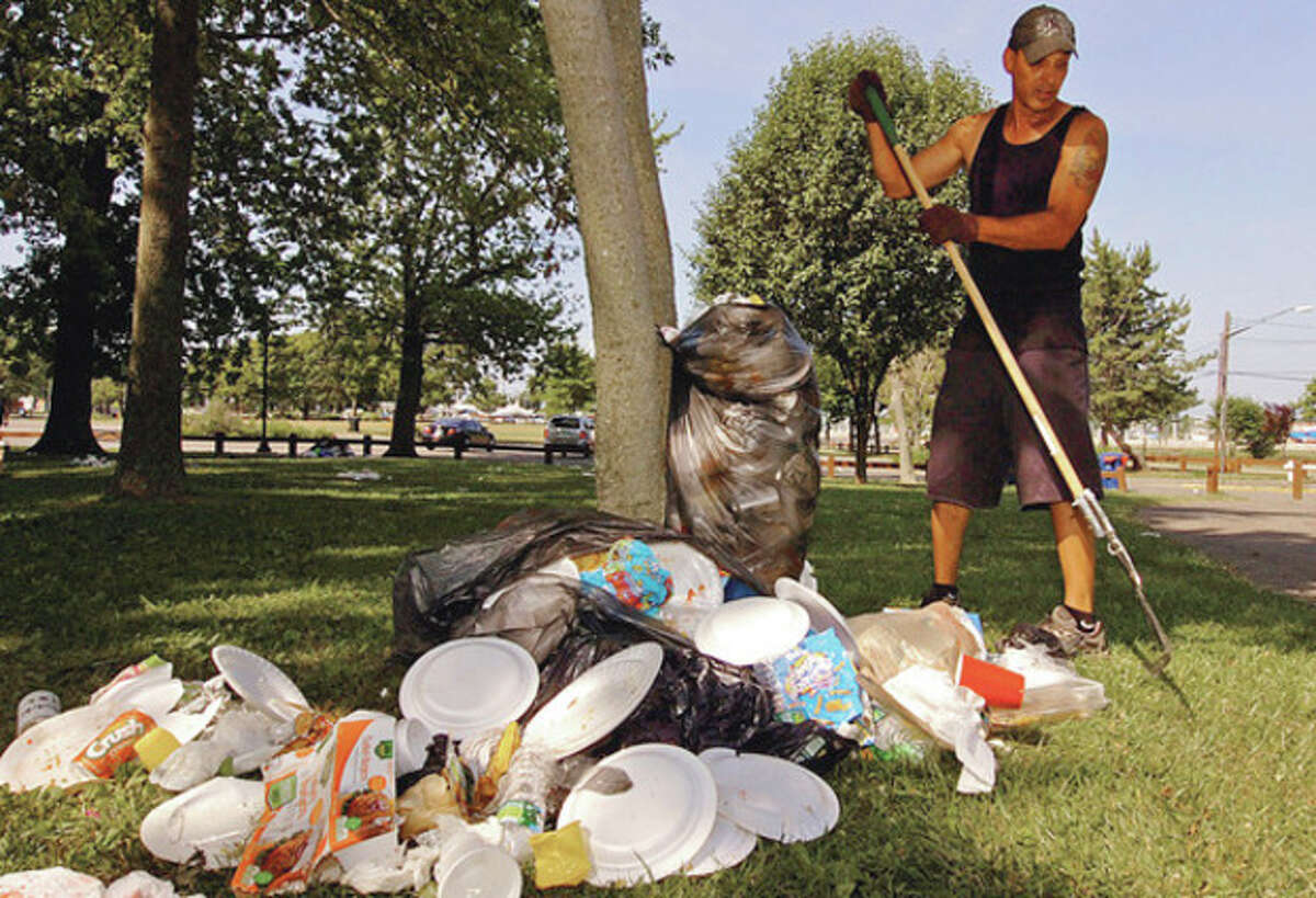 Hour photos / Erik Trautmann In this file photo from 2014, Recreation and Parks employee John Garcia rakes up garbage Thursday morning at Shady Beach following the Independence Day holiday Wednesday when beachgoers jammed the park. Below, garbage piled up Thursday morning at Shady Beach.