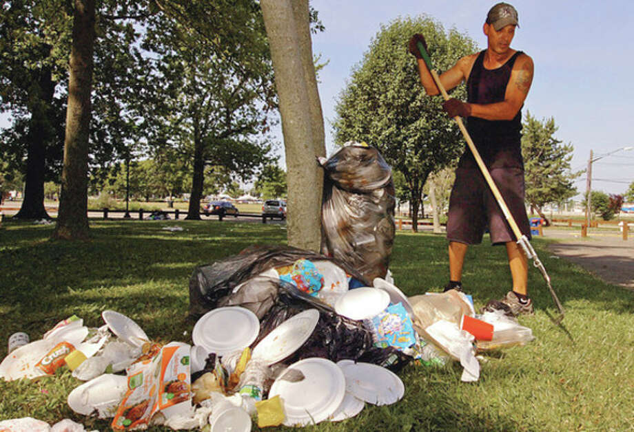 Hour photos / Erik TrautmannIn this file photo from 2014, Recreation and Parks employee John Garcia rakes up garbage Thursday morning at Shady Beach following the Independence Day holiday Wednesday when beachgoers jammed the park. Below, garbage piled up Thursday morning at Shady Beach. / (C)2012, The Hour Newspapers, all rights reserved