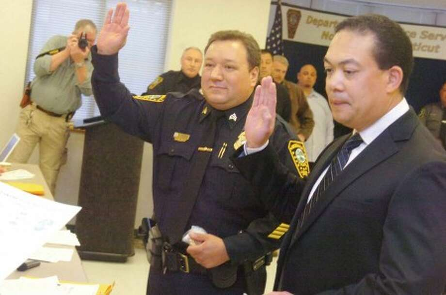 Hour photo / matthew vinci Norwalk police officers Ashley Gonzalez, left, and Shawn Wong Won are promoted to lieutenants Monday at Norwalk Police Headquarters' conference room.