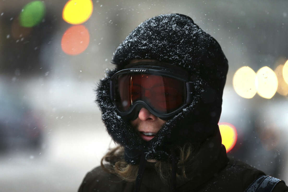 Teresa Goodson walks to work in ski goggles in downtown St. Paul during the first snowstorm of the season on Monday, Nov. 10, 2014. Though the snow will largely stop in Minnesota by Tuesday afternoon, said Joe Calderone, senior forecaster at the National Weather Service office in Chanhassen, Minnesota, the state won't be