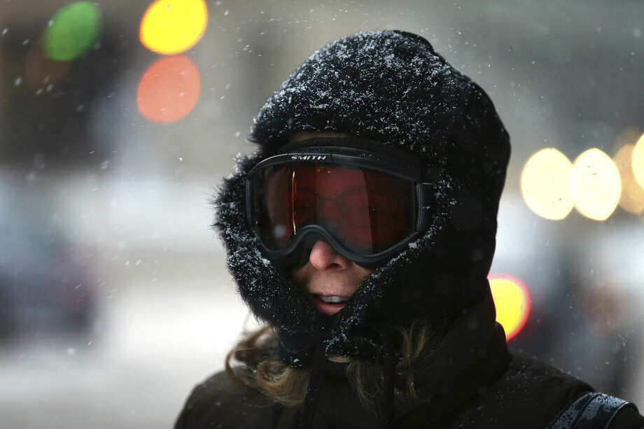 """Teresa Goodson walks to work in ski goggles in downtown St. Paul during the first snowstorm of the season on Monday, Nov. 10, 2014. Though the snow will largely stop in Minnesota by Tuesday afternoon, said Joe Calderone, senior forecaster at the National Weather Service office in Chanhassen, Minnesota, the state won't be """"seeing any warm up any time soon."""" (AP Photo/The Star Tribune, Leila Navidi) MANDATORY CREDIT; ST. PAUL PIONEER PRESS OUT; MAGS OUT; TWIN CITIES LOCAL TELEVISION OUT"""