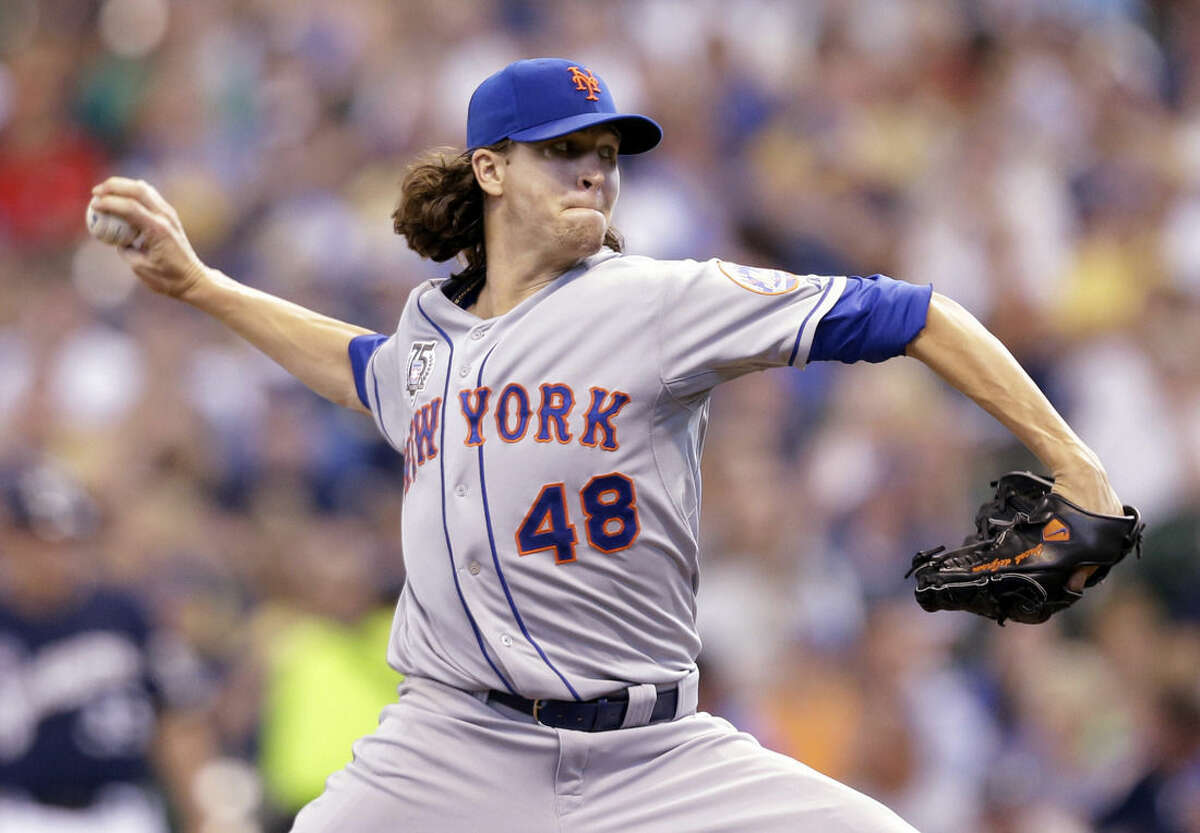 FILE - This is a July 27, 2014, file photo showing New York Mets starting pitcher Jacob deGrom throwing against the Milwaukee Brewers during the sixth inning of a baseball game in Milwaukee. DeGrom has been voted NL Rookie of the Year the Baseball Writers' Association of America announced Monday, Nov. 10, 2014. (AP Photo/Jeffrey Phelps, File)