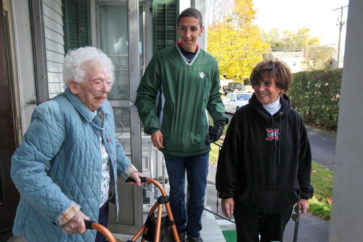 Hour photo/Chris Palermo 104-year-old Doris Pollard, alongside Senior Jacob Alexander and Angela Wax, smiles to see Norwalk High School Athletes clean up her yard Sunday afternoon.
