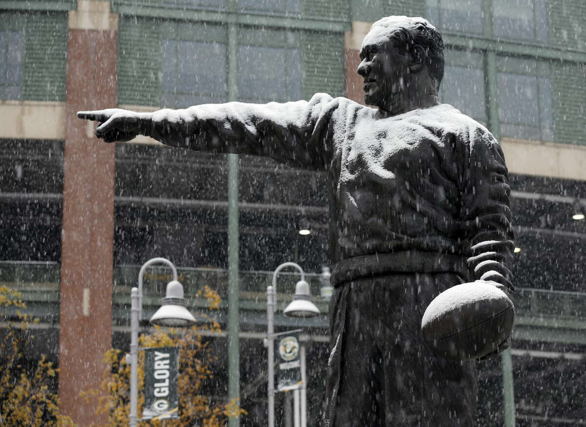Snow falls on the Curly Lambeau statue at Lambeau Field, Monday, Nov. 10, 2014, in Green Bay, Wis. A frigid blast of air is moving into the mainland U.S. thanks to a powerful storm that hit Alaska with hurricane-force winds over the weekend. Residents in the Upper Midwest are bracing for heavy snow and temperatures plunging across numerous states. (AP Photo/Kiichiro Sato)