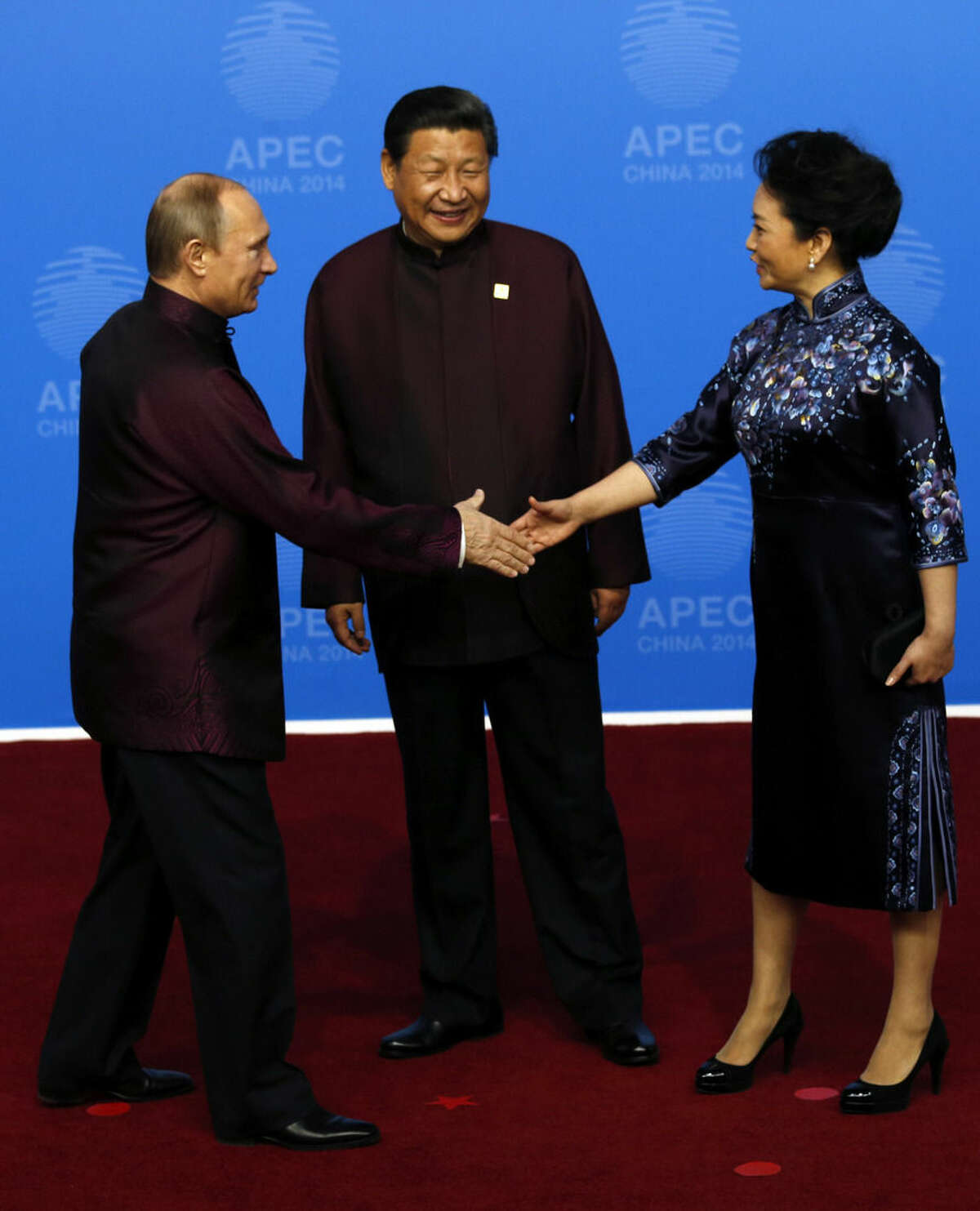 In this photo taken Monday, Nov. 10, 2014, Russia's President Vladimir Putin, left, shakes hands with Chinese first lady Peng Liyuan as Chinese President Xi Jinping, center, watches before a dinner hosted for APEC leaders at the Beijing National Aquatics Center in Beijing. It was a warm gesture on a chilly night when Vladimir Putin wrapped a shawl around the wife of Xi Jinping later in the evening while the Chinese president chatted with Barack Obama. The only problem: Putin came off looking gallant, the Chinese summit host gauche and inattentive. (AP Photo/Ng Han Guan)