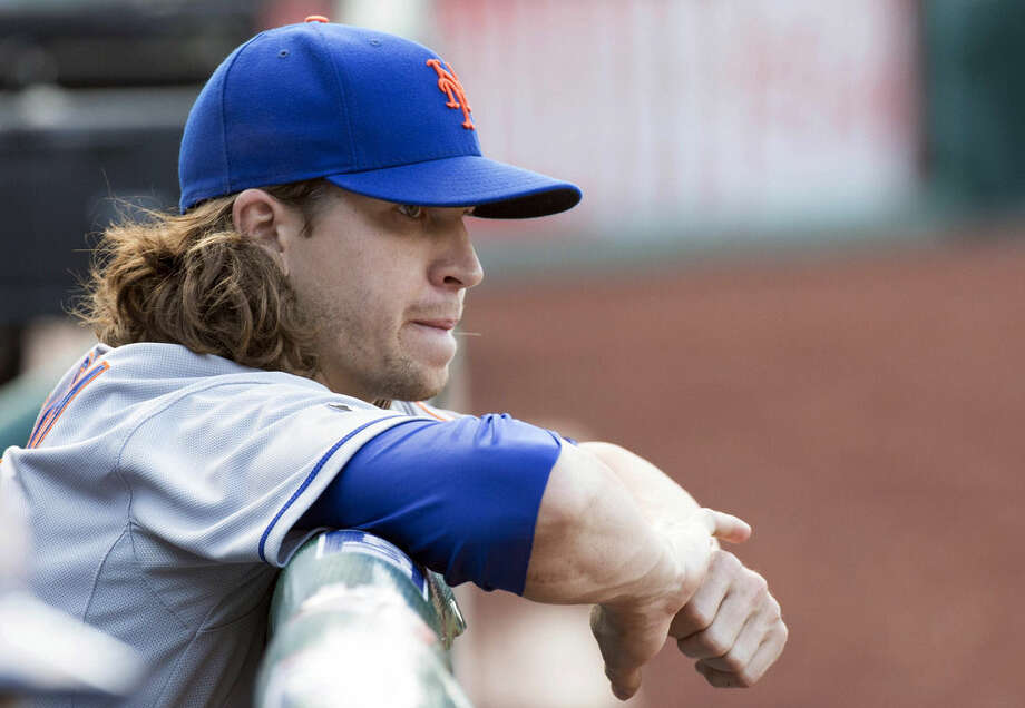 FILE - This is a May 31, 2014, file photo showing New York Mets starting pitcher Jacob deGrom looking on from the bench during the seventh inning of a baseball game against the Philadelphia Phillies in Philadelphia. DeGrom has been voted NL Rookie of the Year the Baseball Writers' Association of America announced Monday, Nov. 10, 2014. (AP Photo/Chris Szagola, File)