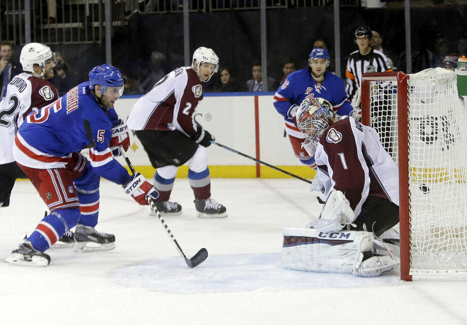 New York Rangers' Dan Girardi (5) shoots the puck past Colorado Avalanche goalie Semyon Varlamov (1), of Russia, for a goal during the second period of an NHL hockey game Thursday, Nov. 13, 2014. (AP Photo/Frank Franklin II)