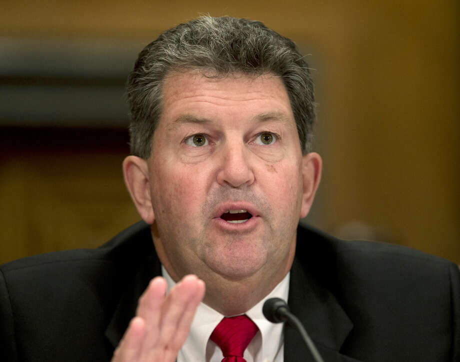In this photo taken Sept. 19, 2013, Postmaster General Patrick Donahoe testifies on Capitol Hill in Washington. Donahoe says he'll retire Feb. 1 after leading the struggling agency for four years. He made the announcement Friday at a meeting of the Board of Postal Governors. (AP Photo/Carolyn Kaster)