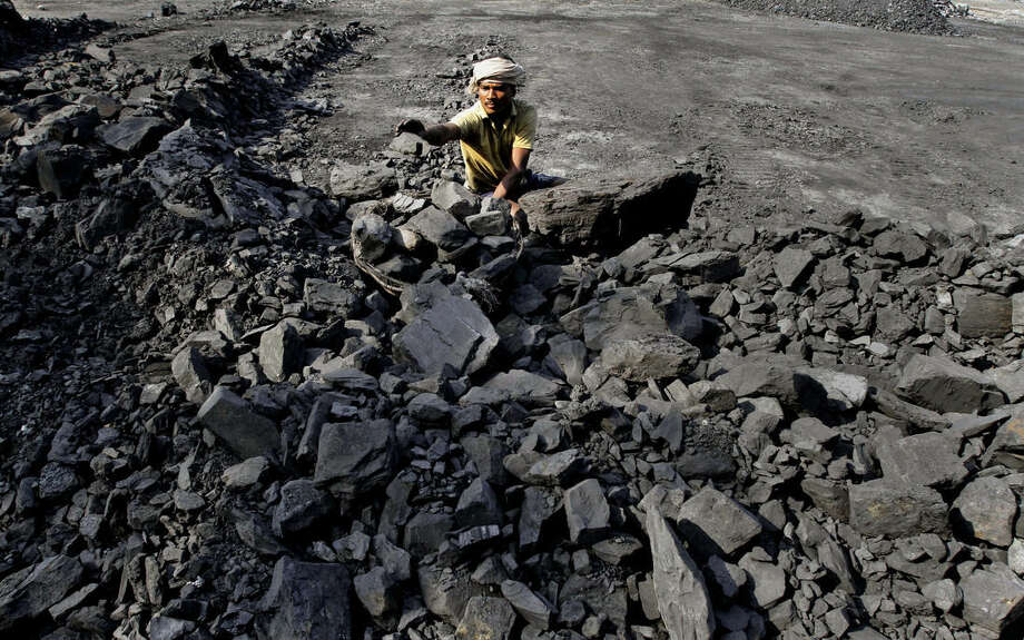In this Thursday, Nov. 13, 2014 photo, an Indian daily wage laborer works at a local coal depot on the outskirts of Cuttack, 25 kilometers (16 miles) from the eastern Indian city of Bhubaneswar, India. This week's China-U.S. climate agreement between the world's top two polluters puts pressure on India, No. 3 on the list, to become more energy efficient and should encourage investment in renewable energy. (AP Photo/Biswaranjan Rout)