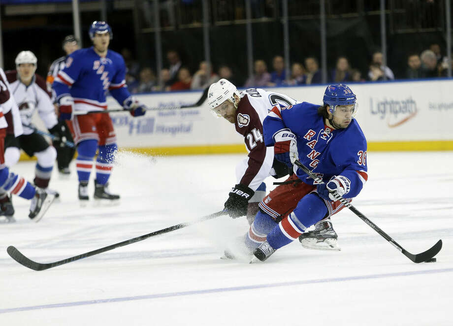 New York Rangers' Mats Zuccarello (36) protects the puck from Colorado Avalanche's Marc-Andre Cliche (24) during the first period of an NHL hockey game Thursday, Nov. 13, 2014, in New York. (AP Photo/Frank Franklin II)