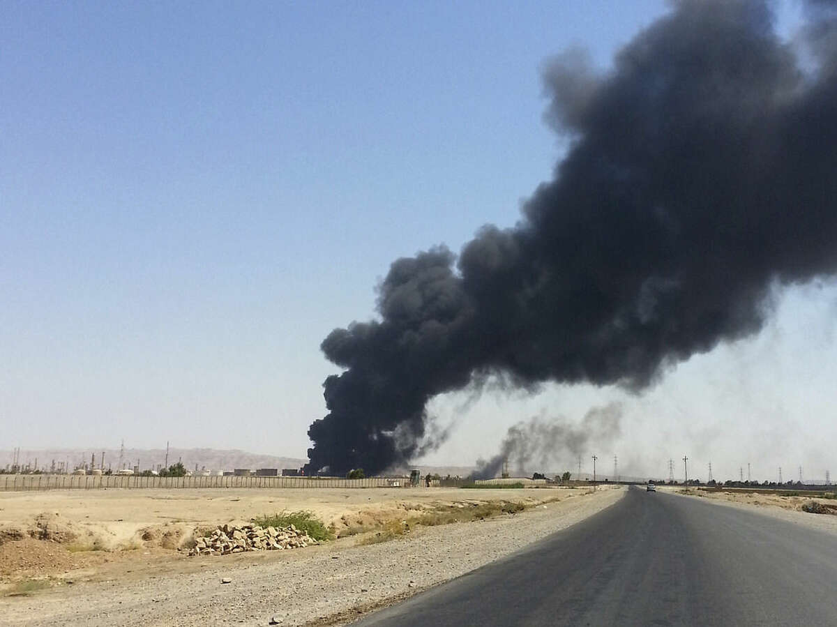 FILE - In this file photo taken Thursday, June 19, 2014, a column of smoke rises from an oil refinery in Beiji, some 250 kilometers (155 miles) north of Baghdad, Iraq. The government forces on Friday, Nov. 14, drove Islamic State militants out from their remaining strongholds inside the oil refinery town of Beiji, two security official said, in a key victory over the terror group that has captured much of northern and western Iraq in a stunning summer offensive. (AP Photo, File)