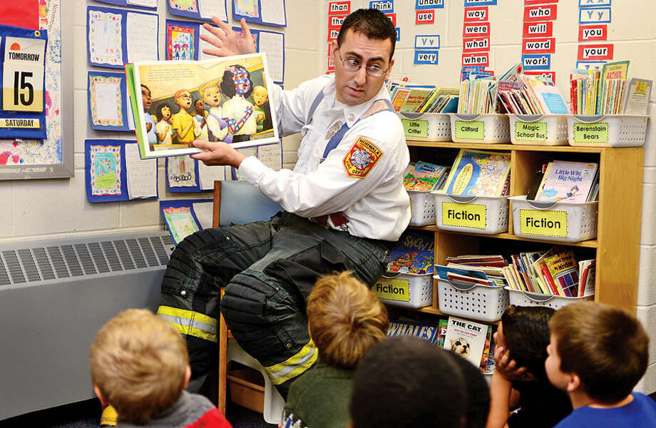 Hour photo / Erik Trautmann Norwalk Fire Department Inspector Luca Feola reads to Fox Run Elementary School students in Ellen Collin's 2nd grade class Friday as part of the Fox Run Loves to Read event.