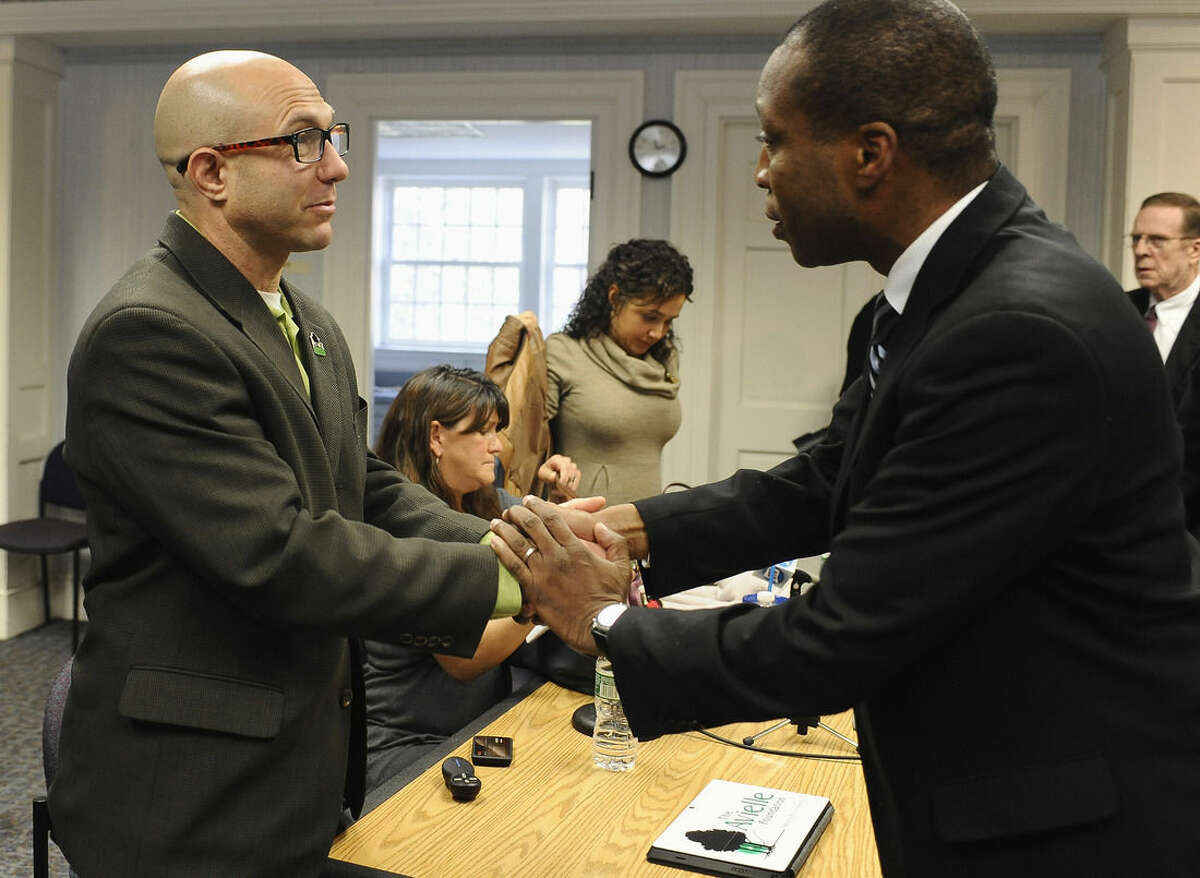 Jeremy Richman, father of Sandy Hook Elementary school shooting victim Avielle Richman, left, shakes hands with Scott Jackson, Chairman of the Sandy Hook Advisory Commission after meeting, Friday, Nov. 14, 2014, in Newtown, Conn. The parents of two children killed made presentations on ways to better address mental health, school safety and gun violence prevention. (AP Photo/Jessica Hill)