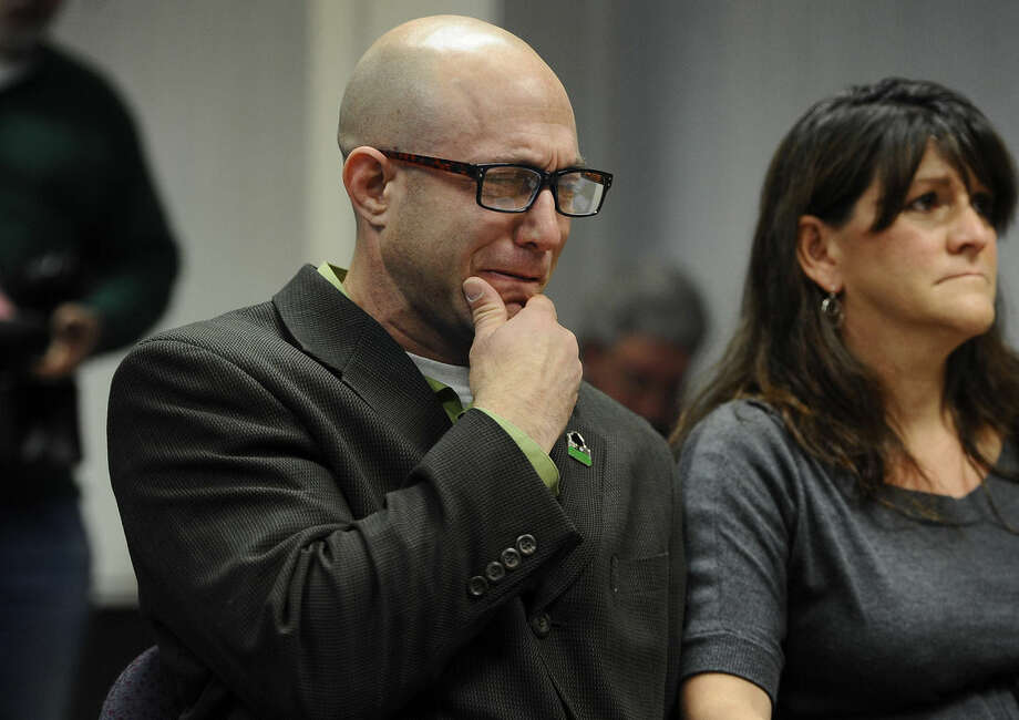 Jeremy Richman, left, weeps as he watches a video of his daughter, Sandy Hook Elementary school shooting victim Avielle Richman as wife Jennifer Hensel, right, sits beside him during a presentation to the Sandy Hook Advisory Commission, Friday, Nov. 14, 2014, in Newtown, Conn. The parents of two children killed made presentations on ways to better address mental health, school safety and gun violence prevention. (AP Photo/Jessica Hill)
