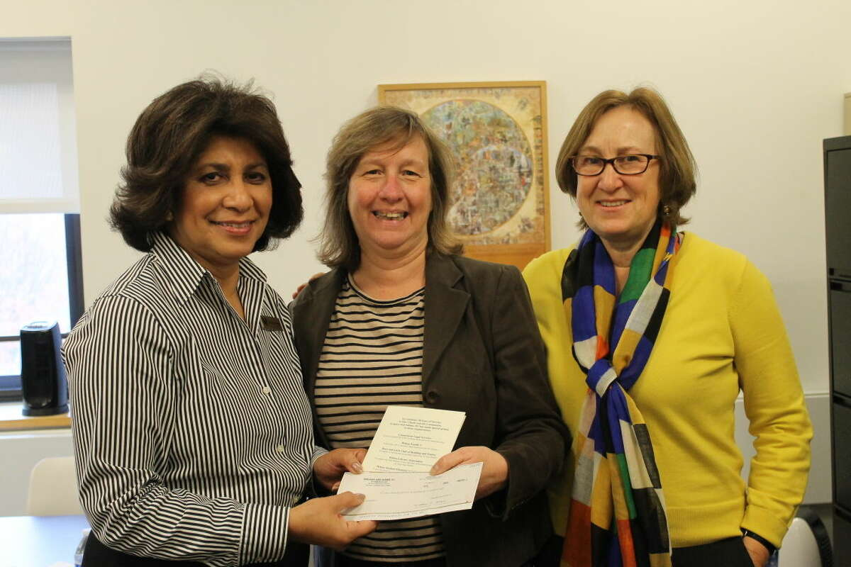 Wilton Library Executive Director Elaine Tai-Lauria (left) and teen librarian Susan Lauricella (right) receive a $2,500 check from Derrell Mason (center), from Gregory and Adams, P.C.