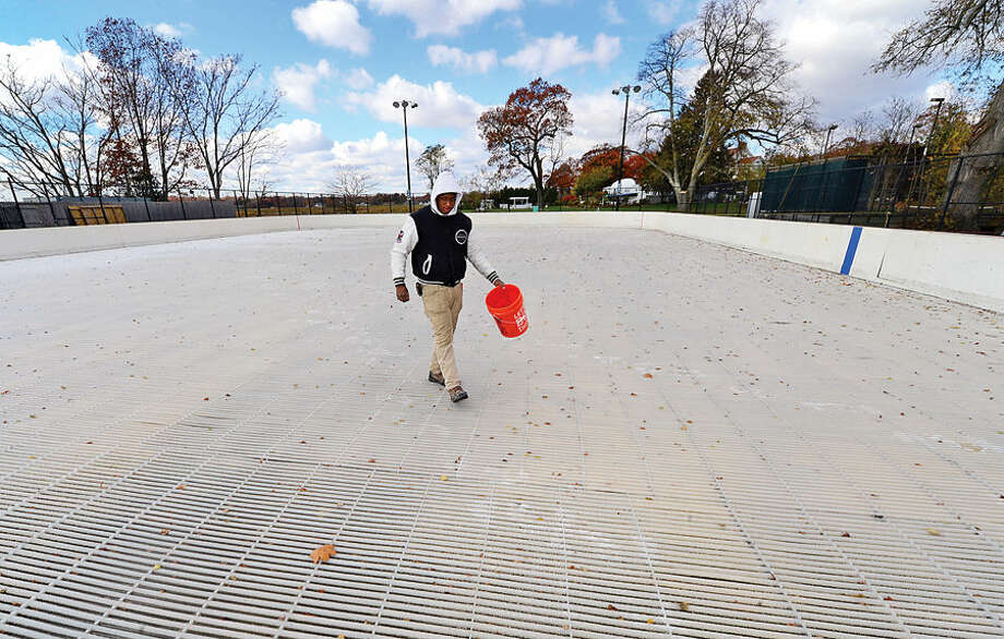 Hour photo / Erik Trautmann Nick Williams helps ready the Westport PAL Ice Rink at Longshore for it's seasonal debut next week.