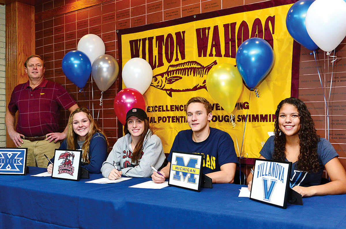 Hour photo / Erik Trautmann Wilton YWahoos coach Randy Erlenbach, left looks over his swimmers; Maggie Kauffeld, Courtney Gilroy, Stephen Holmquist and Samantha Cheruk, as they sign National Letters of Intent to swim for their respective colleges; Xavier, Colgate, Michigan and Villanova, Friday at the Wilton YMCA.