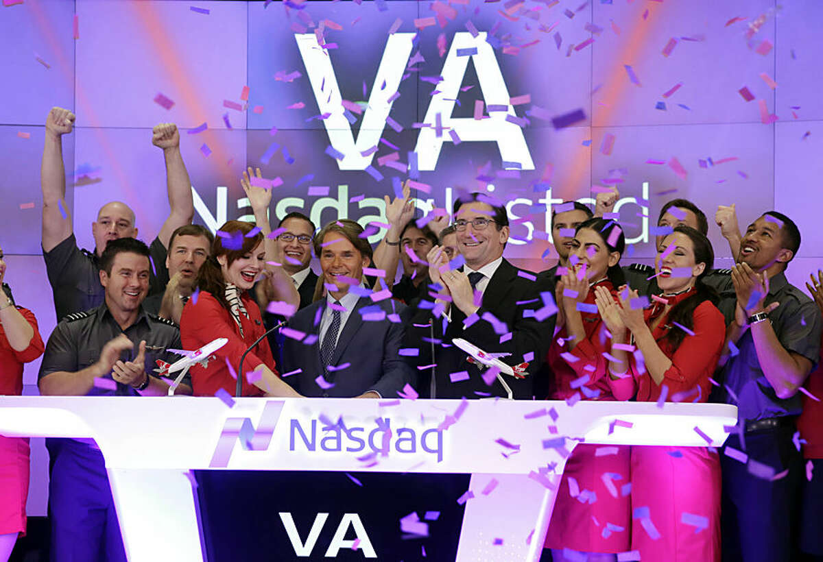 David Cush, third left front row, President & CEO of Virgin America is applauded and showered with confetti as he rings the opening bell at the Nasdaq MarketSite,to mark his company's IPO, in New York, Friday, Nov. 14, 2014. The shares opened at $27, $4 higher than the price that the airline set, and then jumped as high as $29.74 within about an hour of the opening bell.( AP Photo/Richard Drew)