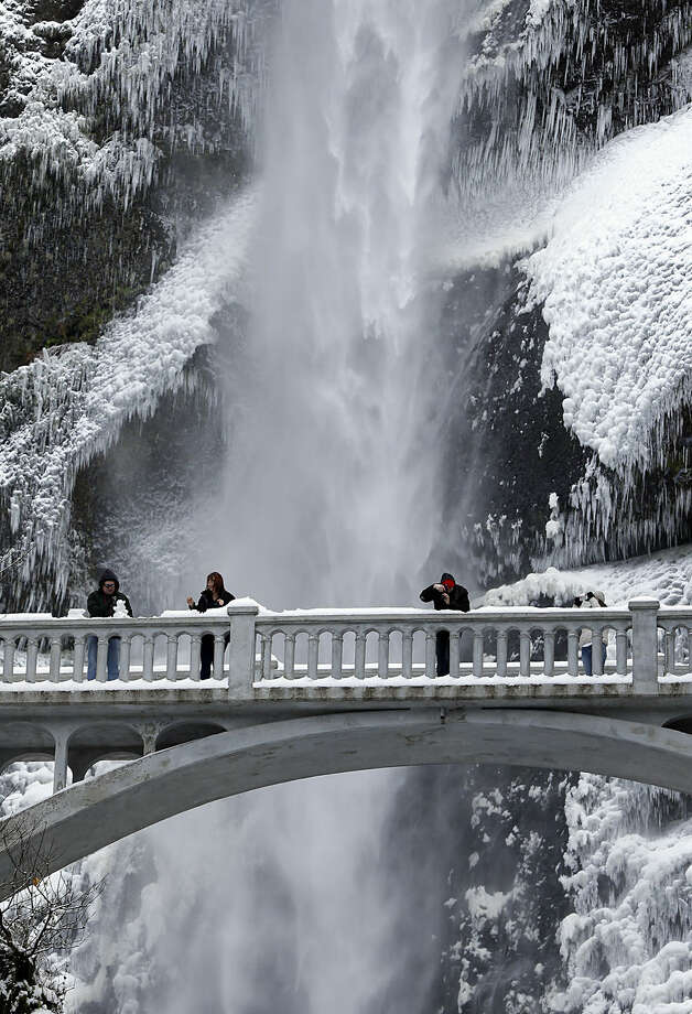 Vistors play with snow and take photos against the backdrop of ice and snow covered walls at Multnomah Falls in the Columbia River Gorge near Bridal Veil, Ore., Friday, Nov. 14, 2014. A Thursday winter storm socked in much of Central and Eastern Oregon, with snow and ice, making travel difficult. (AP Photo/Don Ryan)