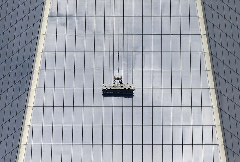 Workers, using a scaffold, replace a window at 1 World Trade, Thursday, Nov. 13, 2014, in New York, the day after two window washers were rescued from a dangling scaffold by firefighters who cut through the pane to reach them. (AP Photo/Kathy Willens)
