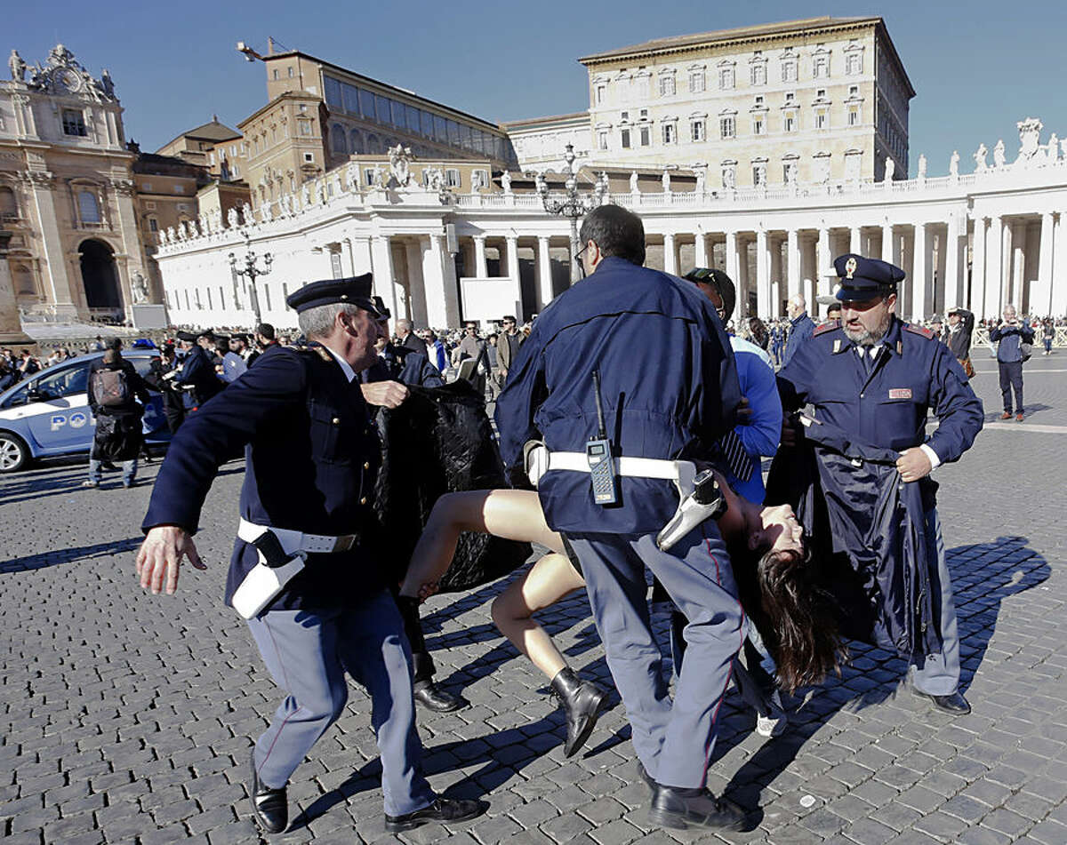 Italian police officers carry away a Femen activist during a protest in St. Peter's Square at the Vatican, Friday, Nov. 14, 2014. Members of the Ukrainian feminist group Femen staged a protest against the upcoming visit of Pope Francis at the European Parliament and Council. (AP Photo)