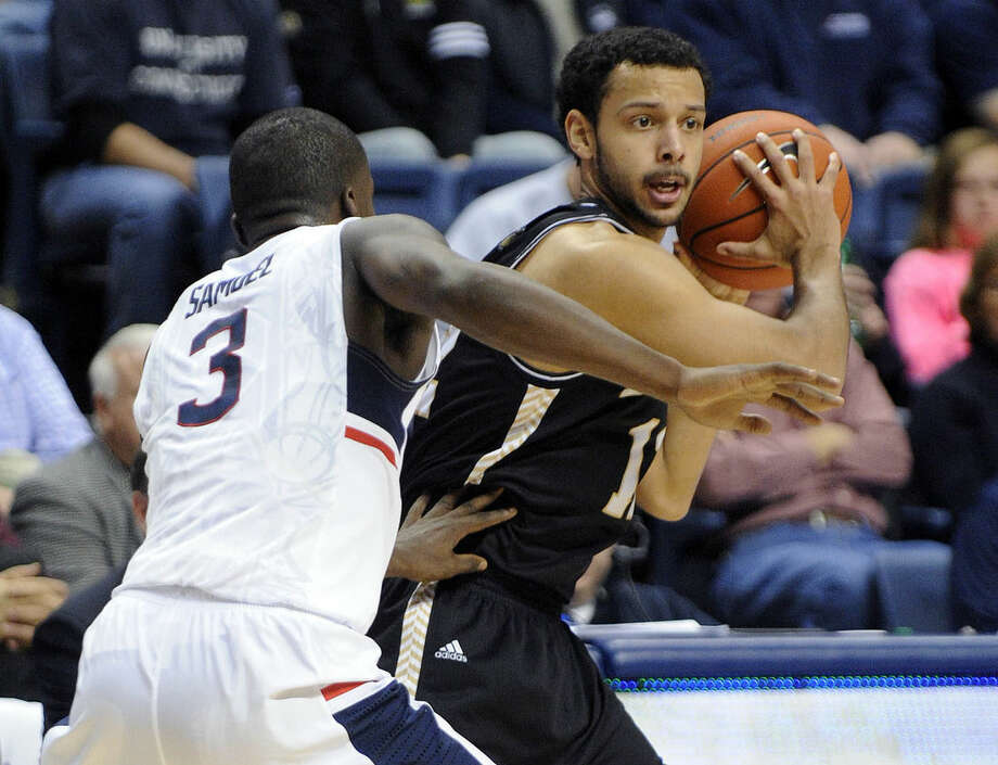 Bryant's Dyami Starks (12) is guarded by Connecticut's Terrence Samuel (3) during the first half of an NCAA college basketball game in Storrs, Conn., on Friday, Nov. 14, 2014. (AP Photo/Fred Beckham)