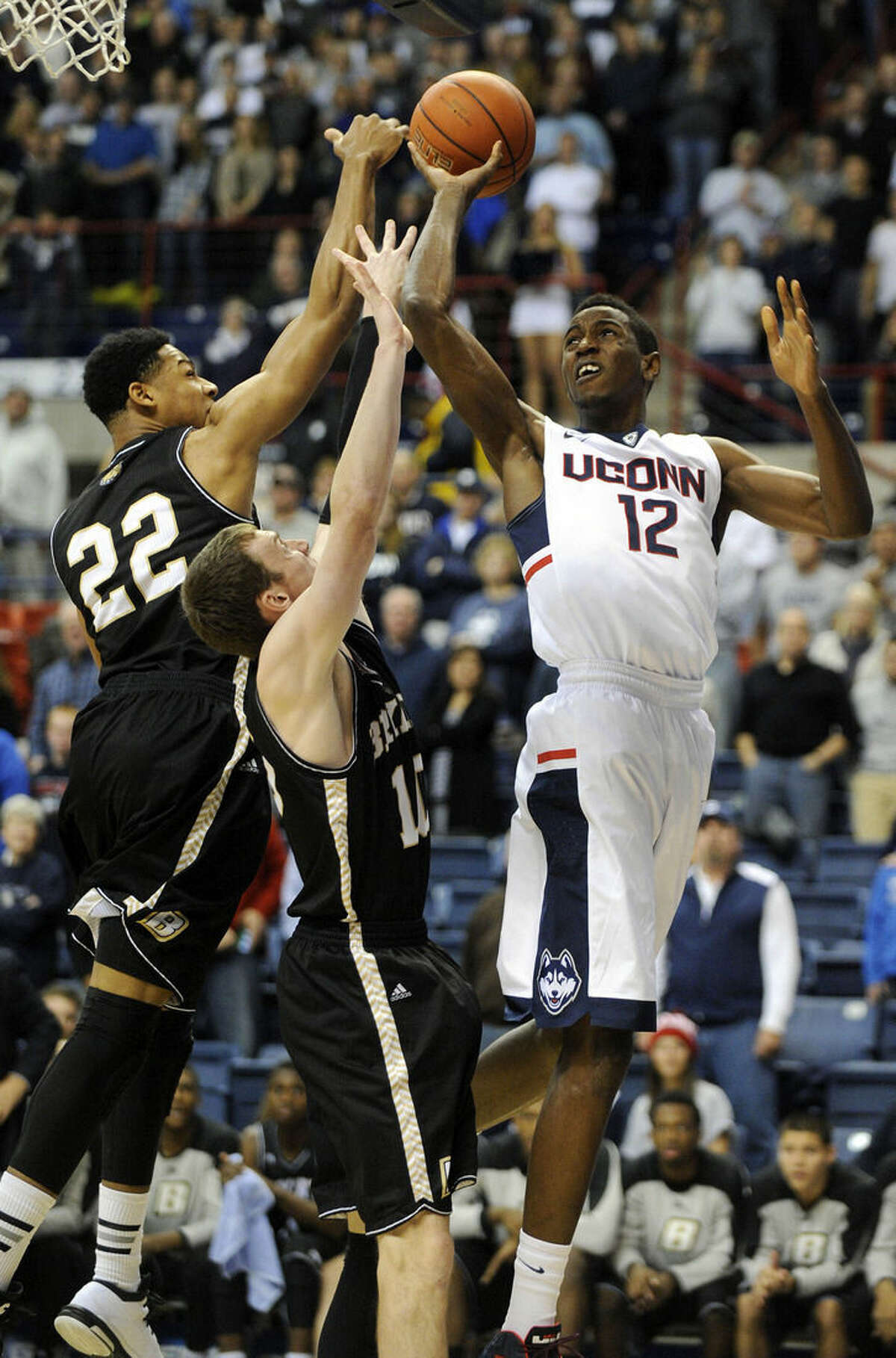 Connecticut's Kentan Facey (12) is guarded by Bryant's Dan Garvin (22) and Joe O'Shea (10) during the first half of an NCAA college basketball game in Storrs, Conn., on Friday, Nov. 14, 2014. (AP Photo/Fred Beckham)