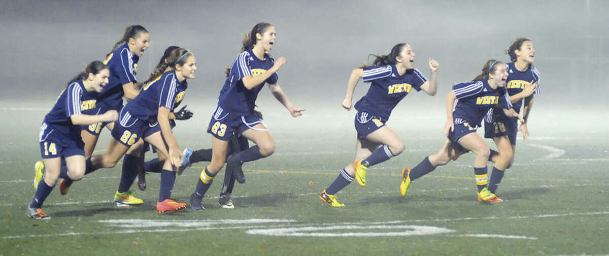 Hour photo/John Nash The Weston girls soccer team raced to celebrate their 2-2 (8-7 PK) win over Suffield in the Class M semifinals. On Saturday, the Trojans get a shot at East Catholic for the state title.
